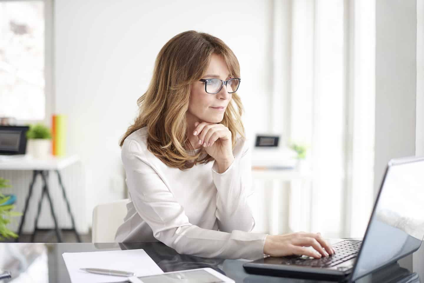 Woman on Laptop Learning How to Start Saving for Retirement