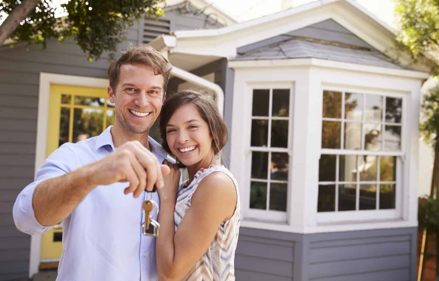 couple holding keys to a new home