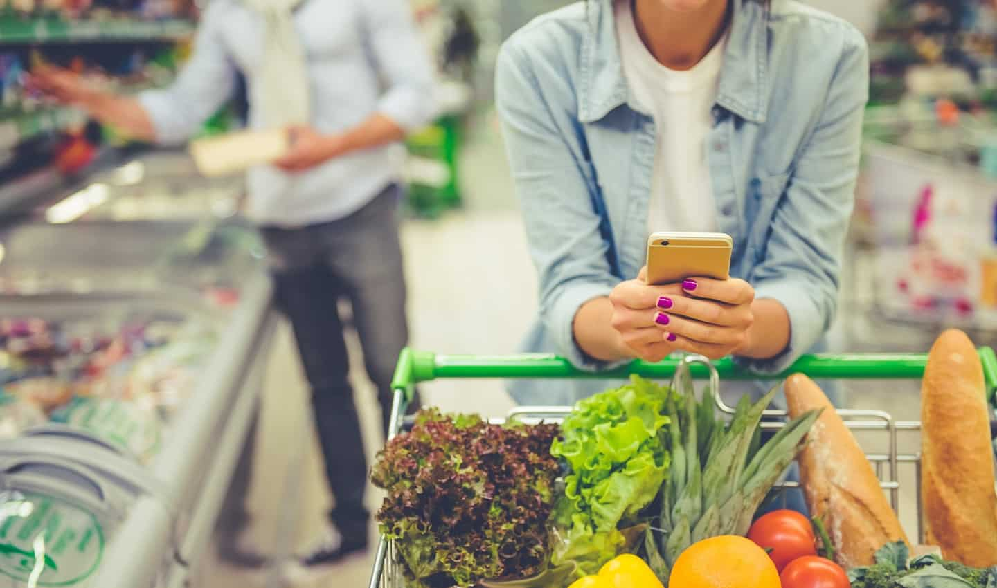 woman searching phone in grocery story for how to save money on food