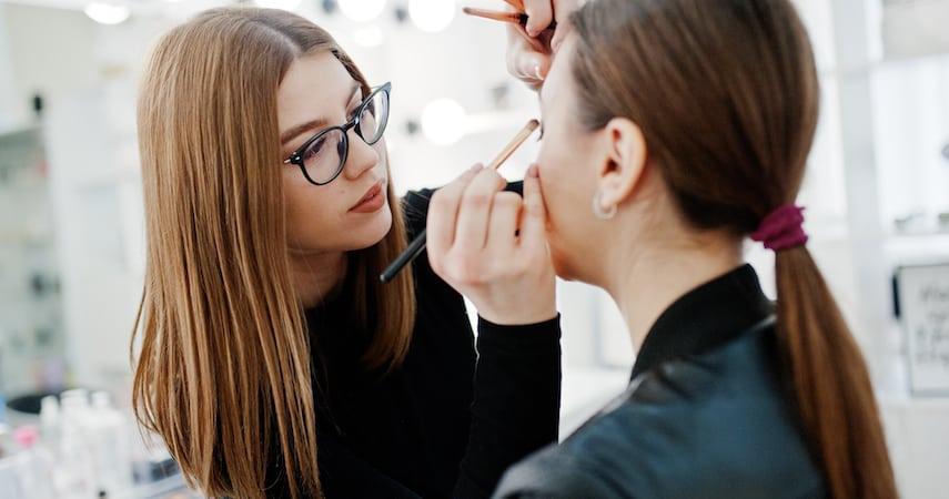 woman doing another woman's makeup AS photo studio
