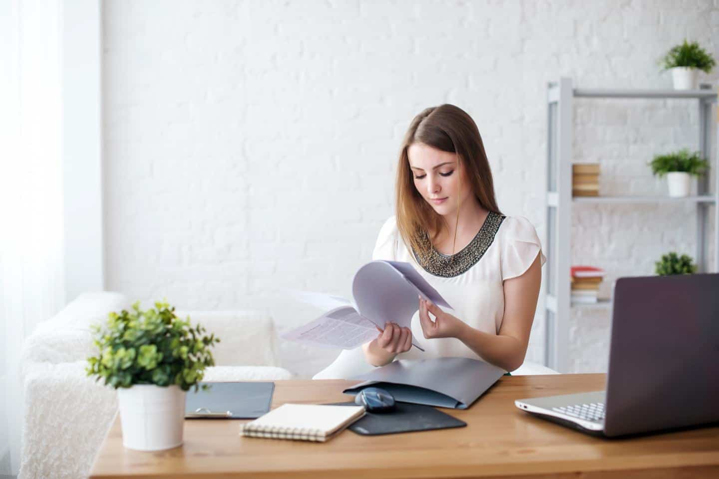 woman flipping through papers at desk
